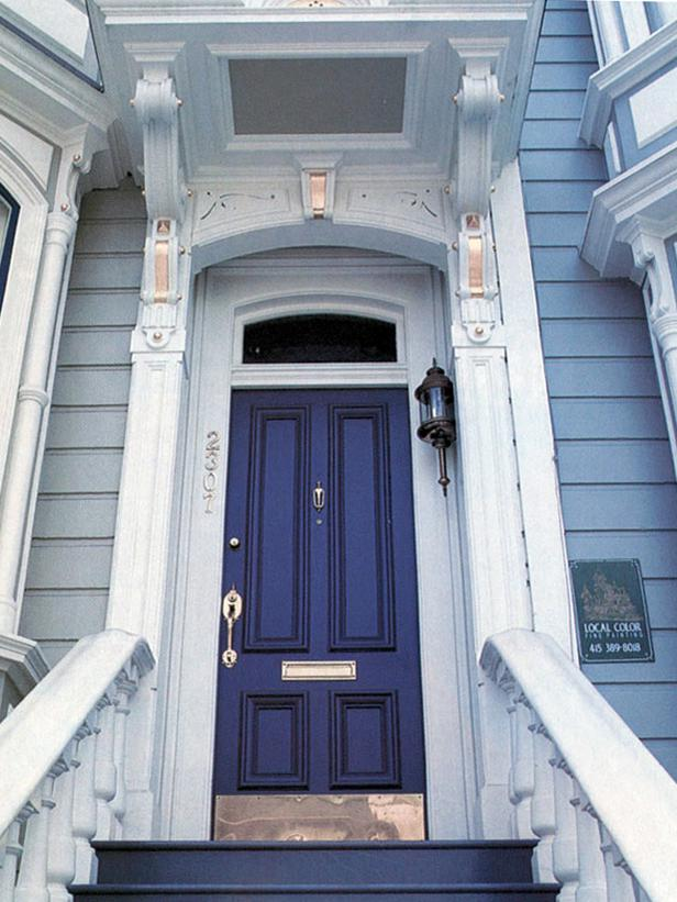 {This indigo front door is a nice complement to the soft blue wood siding on this old house. It has such character!}