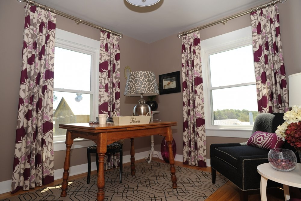 {Patterned curtains hung well above the frame creates the illusion of a longer window and a taller space. Design by:  April Force Pardoe Interiors .}