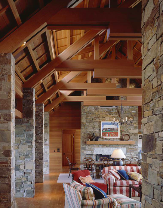 {Pacific Northwest cabin meets traditional nautical nods in this rustic Washington state beach house. Wicker and shiplap take a backseat to the two-story wood-paneled vaulted ceiling and floor-to-ceiling stone, which add depth, texture and richness to the space. From:  Stuart Silk Architects .}