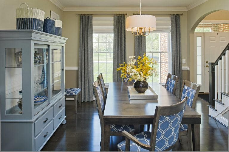 {To offer our client privacy and light filtering benefits, the base layer of these layered window treatments is a soft white roman shade. A custom blue-gray pleated drapery panel highlights the windows' height. From:April Force Pardoe Interiors.}