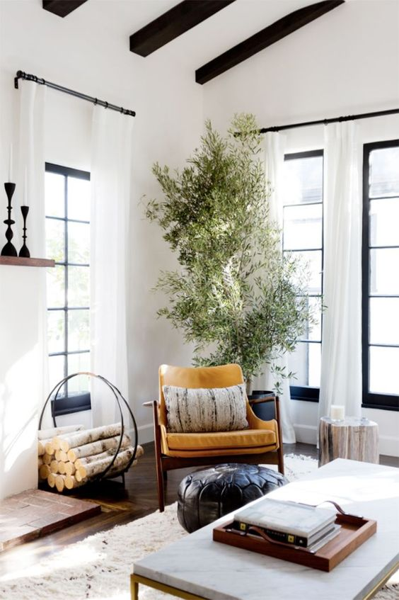 {The matte black window hardware pairs oh-so-perfectly with the painted trim. The choice of color and finish not only emphasize the living room's crisp, simplistic style, but they add a beautiful contrast to the white drapes. From:My Domaine.}
