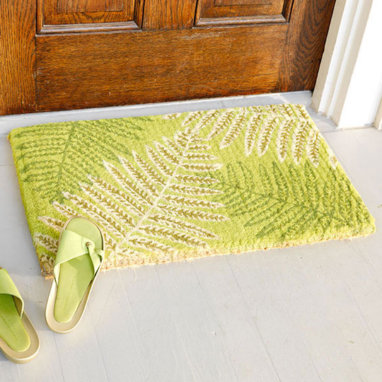 {Spring will welcome you with this green fern mat, found on  apartmenttherapy.com .}