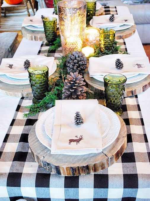 {Tree trunk slices in place of traditional charger plates add an organic layer and an rustic feel, pairing perfectly with the pinecones and loose greens. From: Better Homes & Garden .}