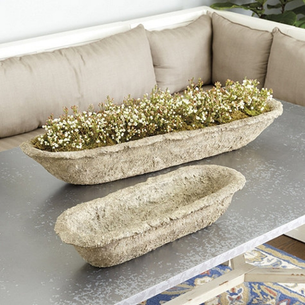 {The volcanic stone material of this trough planter adds a unique element to its design, yet it overall maintains a classic style. From: Ballard Designs.}
