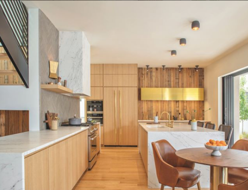 {The brass cabinets add a sophistication and warmth to kitchen's neutral design elements. From:  Luxe Magazine .}