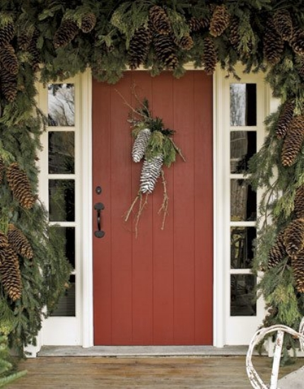 {What a welcoming, seasonal canopy of greenery and pine cones.) From:  Country Living .}