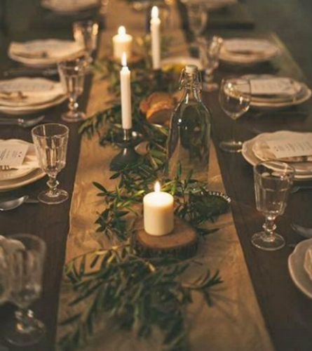 {Holiday tablescapes made super simple: lay bunches of evergreens along the length of your dining table. For added glow,space out votive or tapered candles.From:  Harpers Bazaar .}