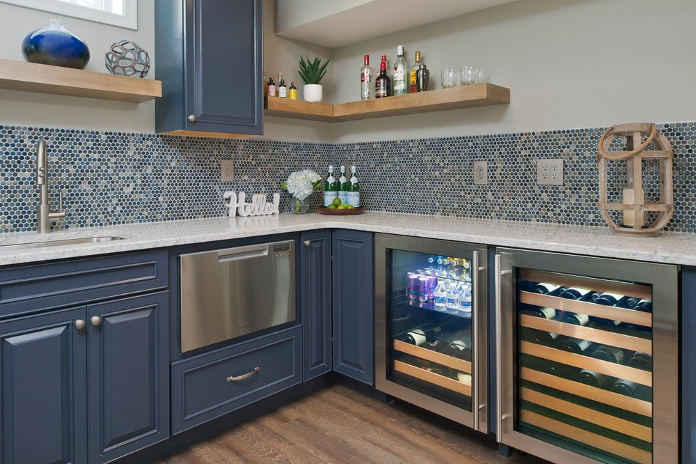 Wine fridge installed in blue cabinets under counter top