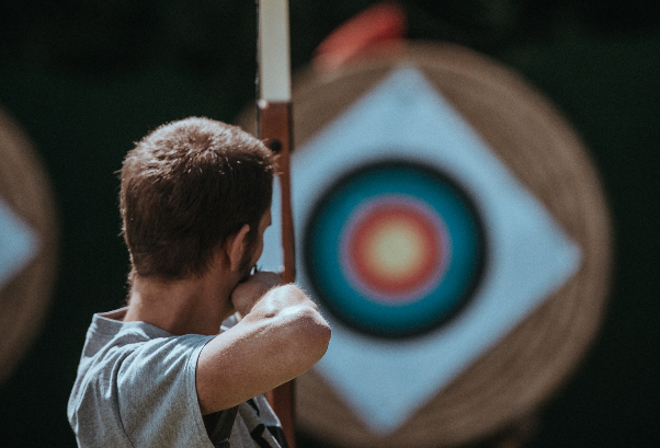 Image of a person with a bow and arrow looking at an archery target
