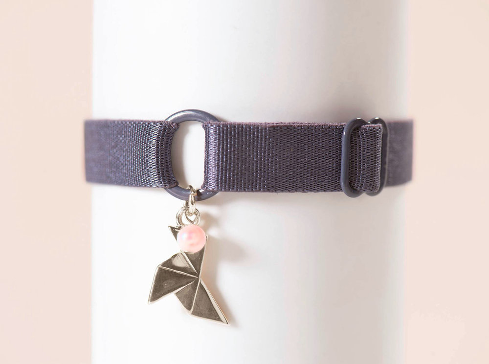 Première collection : la cocotte en argent de nos colliers avec une perle sur une bretelle de soutien gorge taupe