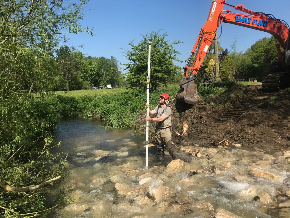 An operative checks the levels to ensure that the gradient is gentle enough  for fish to be able to migrate up and downstream.