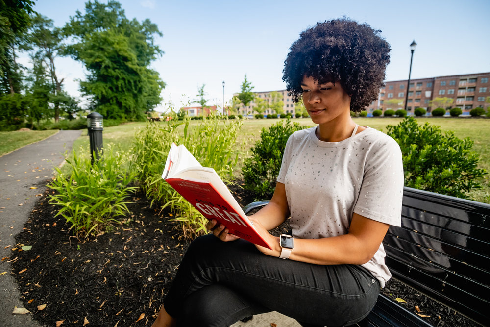 a woman reading on a bench at jordan's branch trail
