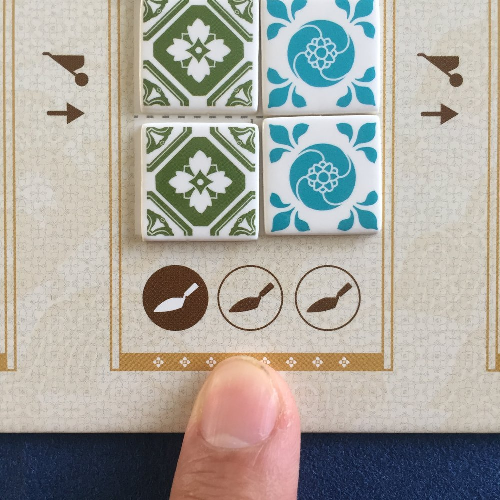 A5.  One tile must be pushed to the design card (dark trowel). Two tiles may be pushed to the design card (light trowels). We'll push three trowels up. Leaving three left over tiles. See next image.