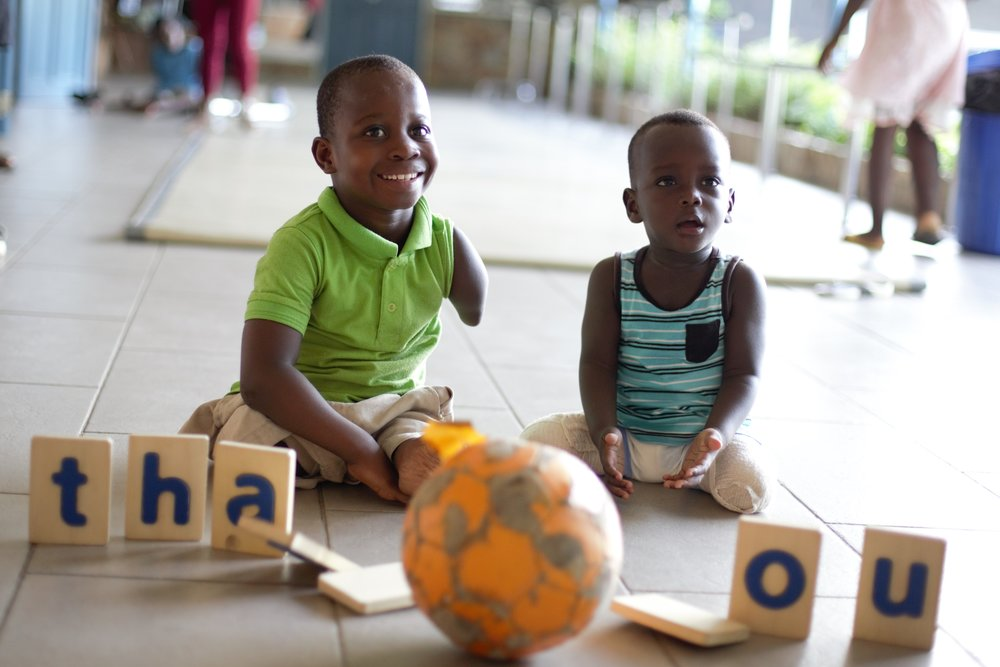 Blessing and Kobe, Two Children in the Care of the Orthopedic Training Center in Ghana, West Africa, Express Their Gratitude For Project Lolo's Support with Tumbling Block Letters.  Credit: Orthopedic Training Center (OTC)