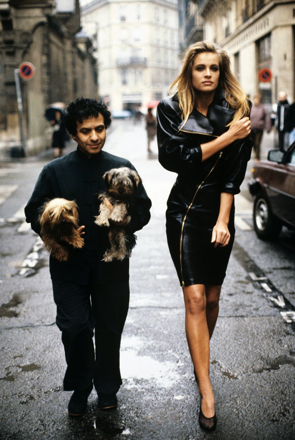 Fashion designer Azzedine Alaïa holding his two Yorkshire terriers, Patapouf and Wabo, walking in Paris street with model Frederique who wears one of his creations, a black leather zippered dress, 1986. Photograph Courtesy of Arthur Elgort.