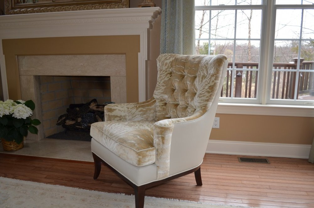 Beige and white printed tufted couch and a fireplace