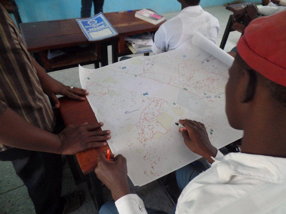 A student identifying geographical features and landmarks on the Kano state Land-use map