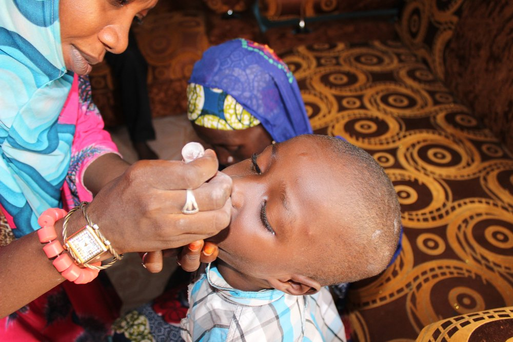 A health worker vaccinates a child with the Oral Polio Vaccine