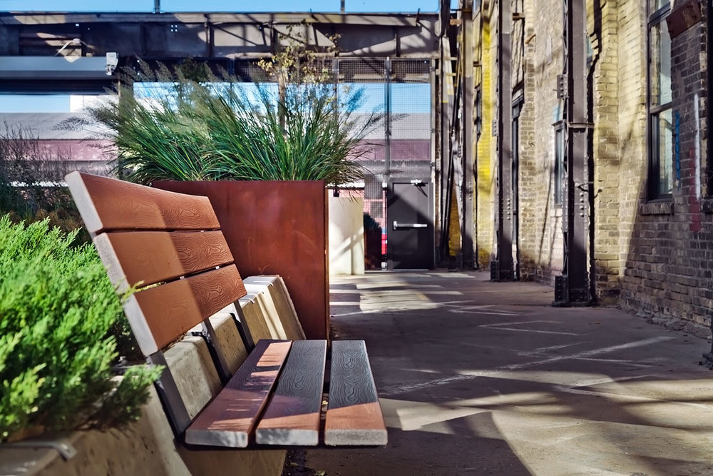 The sloped concrete planter walls become the foundation for comfortable, integral benches.