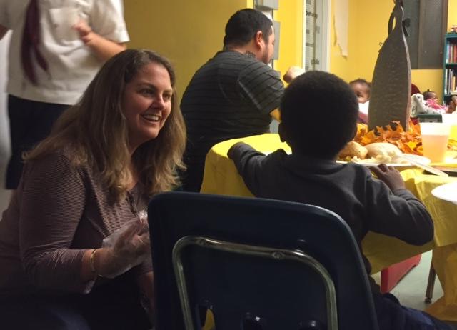Compass Family Shelter volunteer serving Thanksgiving dinner.