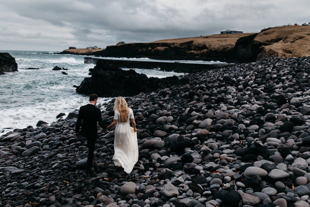 Hannah & Jeff both love getting lost in breathtaking landscapes, and wanted an intimate wedding rooted in nature and adventure. Hannah had been intrigued by Iceland for years, so they decided to get married in the little black church at Hotel Budir, on Snaefellsnes Peninsula. Originally planning to elope, Hannah & Jeff ended up bringing a group of their dearest family and friends along for this magical day. As a florist, Hannah spent the morning with her business partner creating little arrangements in a sunroom overlooking the bay and lava fields. It was just the right size for these personal touches to be manageable, which was so important to her.