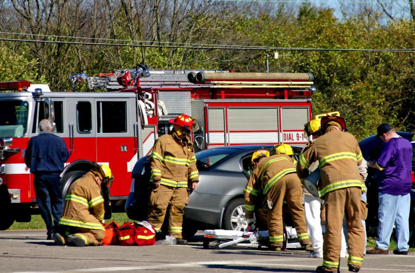 A car crash victim being helped by firemen needs assistance from Marietta personal injury lawyers.