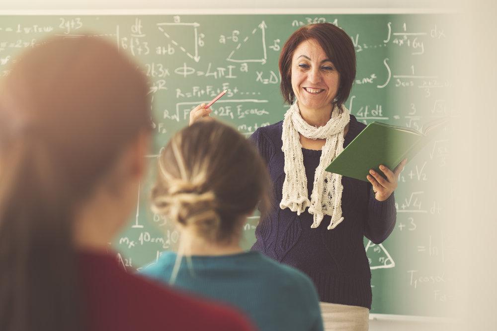 Teacher in front of classroom.jpeg