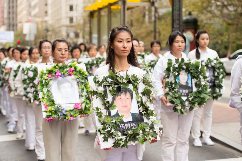 海外法輪功學員手持被中共迫害致死的法輪功修煉者遺像參加遊行。(戴兵/大紀元)