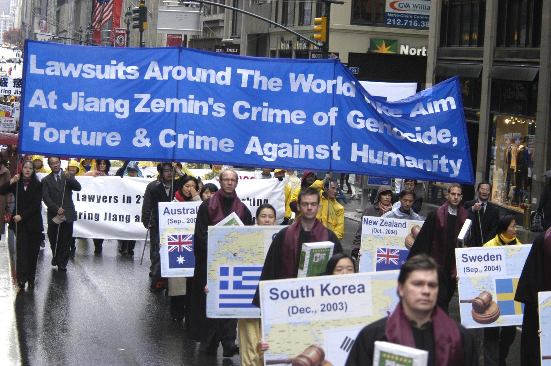"""2004年11月20日,法輪功在紐約曼哈頓舉行遊行,聲援訴江大潮。(明慧網) November 20, 2004, Falun Gong practitioners held a grand parade in Manhattan, New York City. Among the various sections of the parade, one section entitled, """"Bring Jiang Zemin to Justice,"""" drew a lot of attention."""