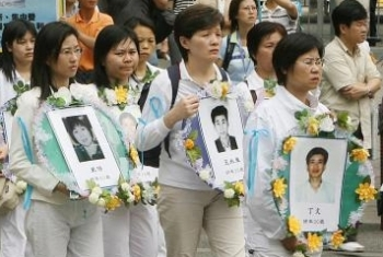 Women hold photos of Falun Gong practitioners who have died in Chinese prisons during a ten year persecution by the Chinese regime. (Mike Clarke/AFP/Getty Images)