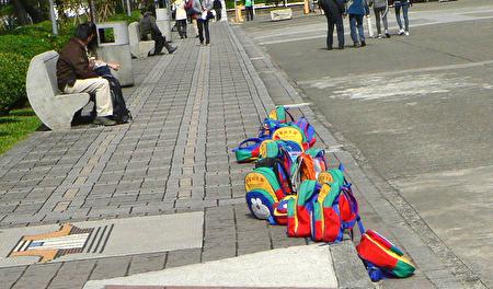 臺北國父紀念館地上,一堆無人看管的小書包。書包的主人們──一群臺北漢家幼稚園的小朋友們,到別處玩耍去了。(曾錚攝影)