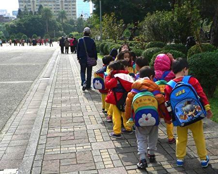 小朋友們遊玩結束後,撿起地上的書包,列隊離開。(曾錚 攝影)