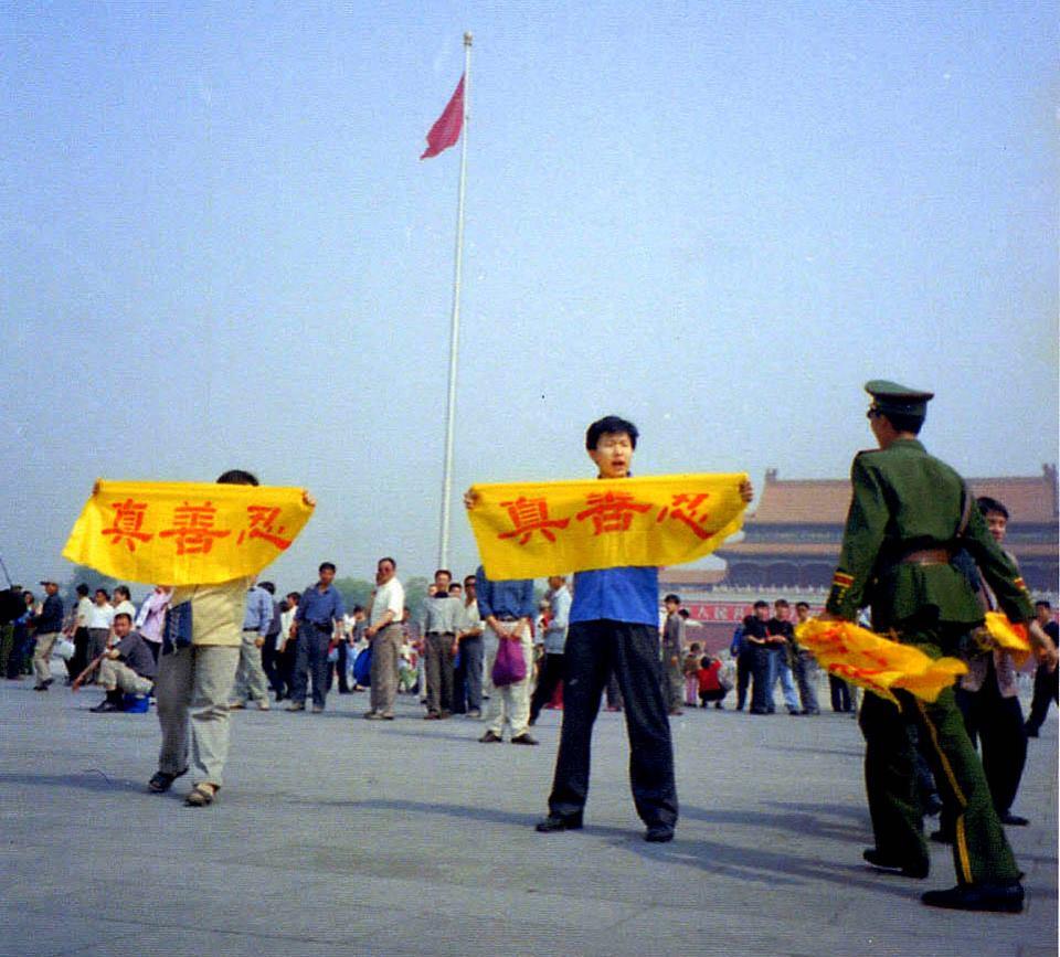 """Nesta foto sem data, praticantes do Falun Gong na China exibem faixas onde se lê """"Verdade-Benevolência-Tolerância"""" enquanto um policial se aproxima para prendê-los (©Minghui.org)"""