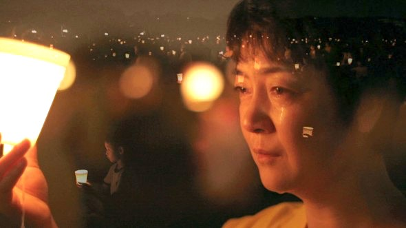 "Jennifer Zeng sits at a candlelight vigil held for persecuted and killed Falun Gong practitioners in China. Zeng's story is told in ""Free China: The Freedom to Believe,"" which will be in theaters in Los Angeles on May 31 and in New York on June 7. (Screenshot from ""Free China"" trailer)"