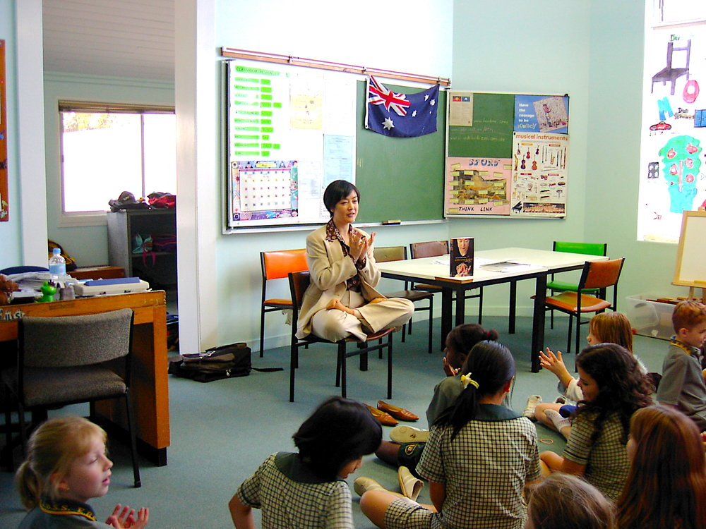Jennifer demonstrating Falun Gong's  Lotus Hand Position to students at  East Brisbane State School on May 26, 2005