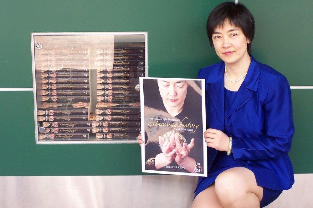 曾錚2005年在澳大利亞黃金海岸一家櫥窗裏擺滿曾錚英文版自傳  Witnessing History  的書店前手持書店宣傳海報留影。