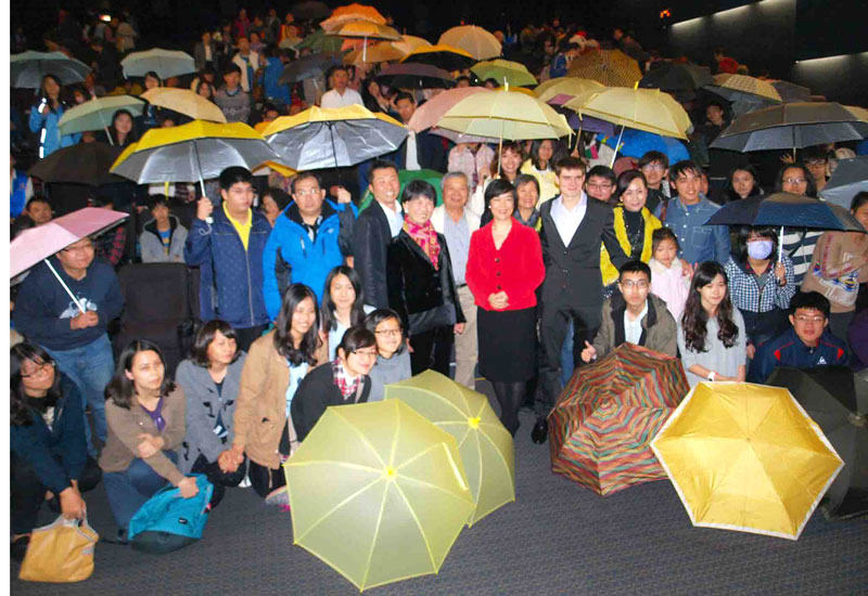 "Ben Hedges and Jennifer Zeng taking a group umbrella photo with audience after a "" Free China "" screening in Taipei on Dec. 5, 2014 in support of the Hong Kong people's efforts for democracy."