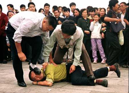 美聯社照片:在眾目睽睽之下,一名便衣警察用皮鞋踩著一名手無寸鐵的學員的臉,另一名警察則一邊踩學員的腿一邊將一個小刀按到學員的脖子上。