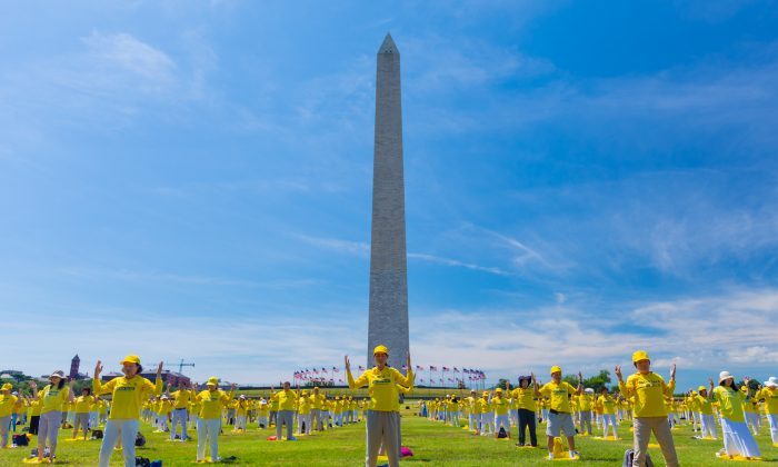 Falun Gong practitioners demonstrate the disciplines exercises in front of the Washington Monument on July 19, 2018. (Mark Zou/Epoch Times)