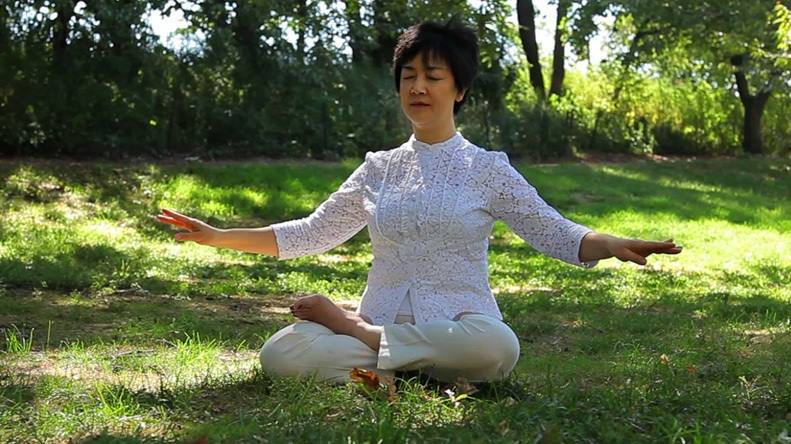 Screenshot from Free China movie showing Jennifer doing the 5th exercise of Falun Gong,   Reinforcing Supernatural Powers  .
