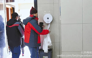 A Chinese man taking toilet paper from a public restroom in Beijing. 一名北京人正在卷走公廁中的手紙。
