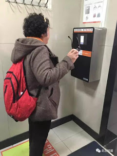 A Chinese woman standing in front a face-scanning machine to wait for her face to be scanned. The paper is only available after the scan finishes. 一名北京婦女站在「人臉識別廁紙機」前等待。機器完成「識別」她的臉之後,手紙才會出來。