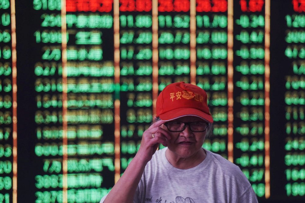 An investor stands in front of a screen displaying stock market figures at a securities company in Hangzhou in China's Zhejiang Province on June 19, 2018. Shanghai and Hong Kong stocks plunged on June 19 on investors' fears that the US and China could be heading for a full-blown trade war following tit-for-tat tariff threats. (-/AFP/Getty Images)