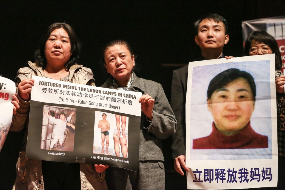 Falun Gong practitioners of Washington hold pictures of family members or lawyers still imprisoned in China for practicing Falun Gong or defending Falun Gong at the at the press conference to announce the Formation of The Coalition to Advance Religious Freedom in China (CARFC) at The Congressional Auditorium in the Capitol Visitor Center, Washington, on Mar. 4, 2019. (Jennifer Zeng/The Epoch Times)
