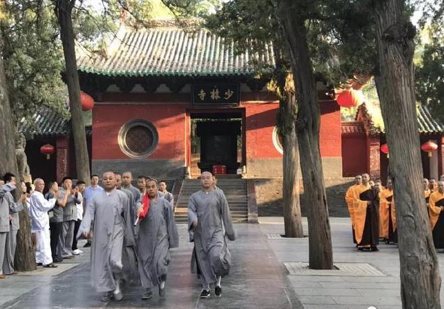 "Monks in the famous Shaolin Temple in Henan Province in China march with a Chinese flag during a ""Flag Raising Ceremony"". All religious groups in China are required to love the CCP first before they can love or worship their God or Buddhas. 河南少林寺和尚在舉行升旗儀式。在大陸,宗教人士被迫先愛黨,然後才能愛他們的上帝或神佛。"