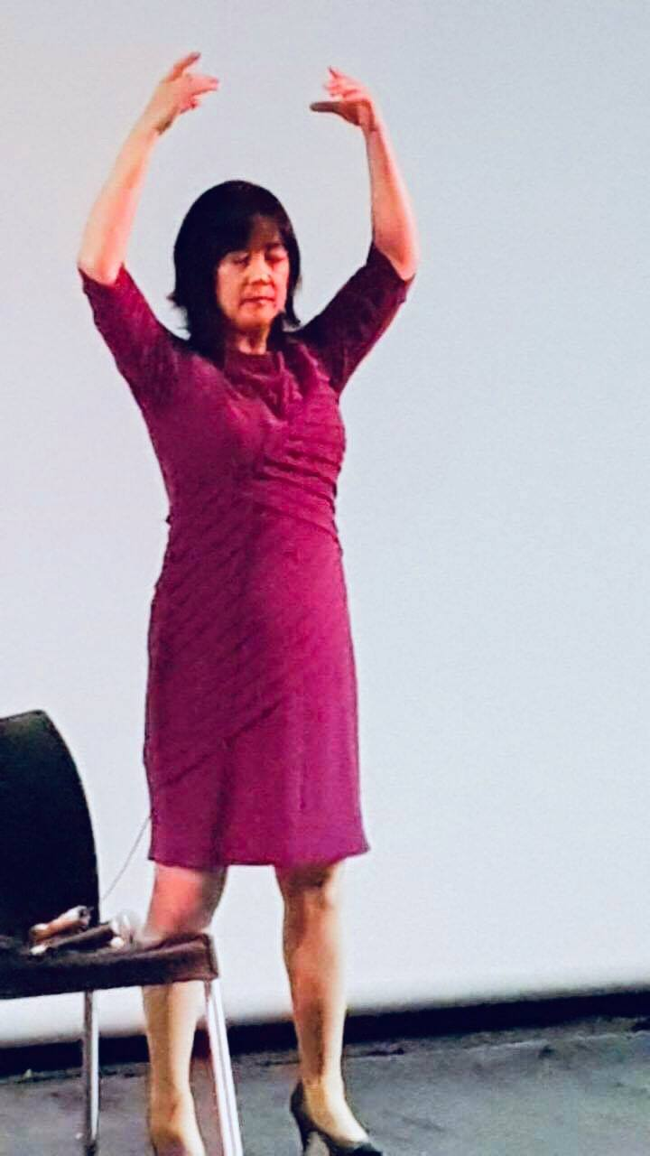 """Jennifer Zeng demonstrating the second exercise of Falun Gong, Falun Standing Stance( http://en.falundafa.org/eng/html/dymf_2014/dymf_2014_2.htm#2 )  at the panel discussion after the screening of the movie """"Free China"""" at the Tel Aviv Cinematheque."""