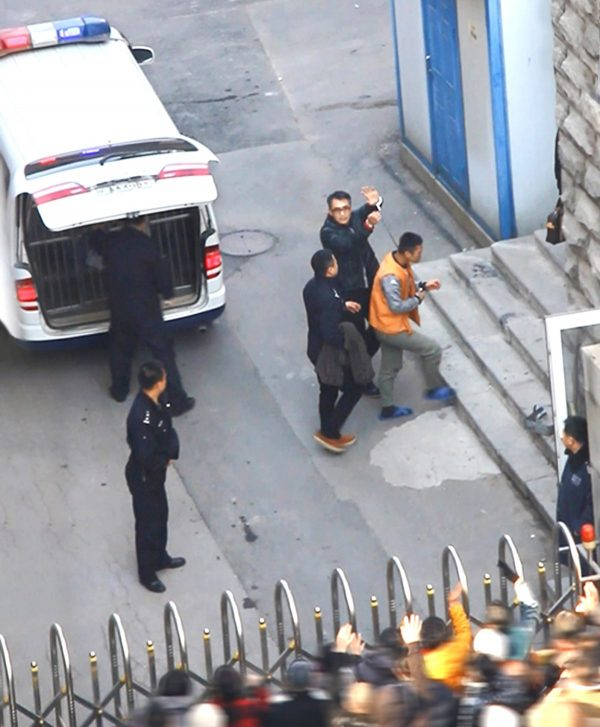 Yu Ming holds up his handcuffed hands and waves as he arrives at the court in Shenyang City on Nov. 20, 2014. (Minghui.org)