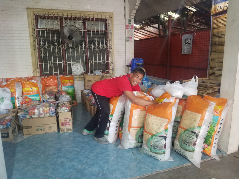 Pastor Bonnie proudly showing the large bags of food God provided