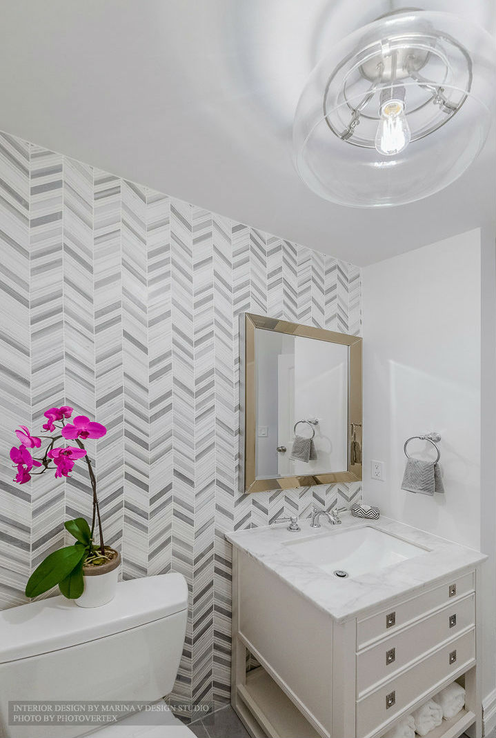 Powder room with unique tiled focus wall and glass ceiling fixture