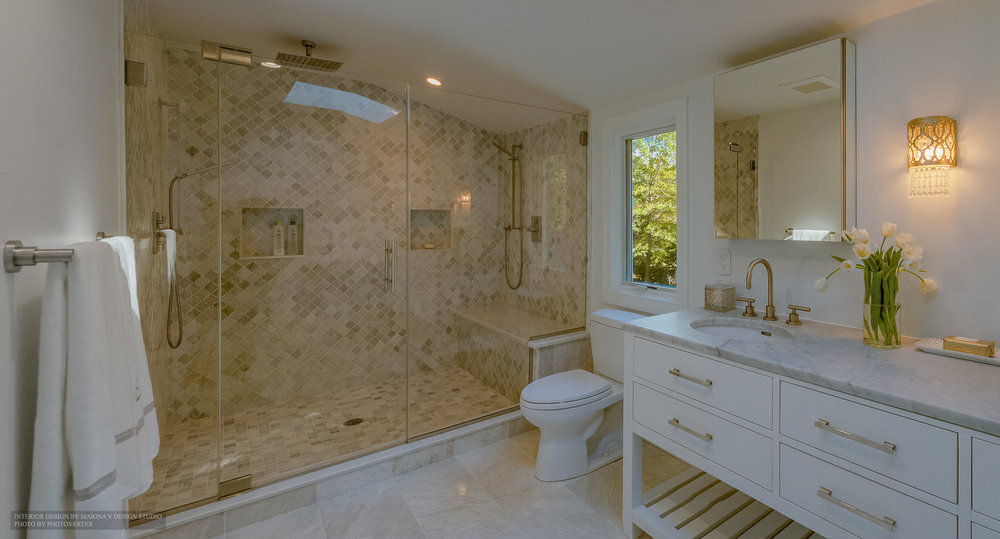 Bathroom interior with toilet between sink counters and shower room